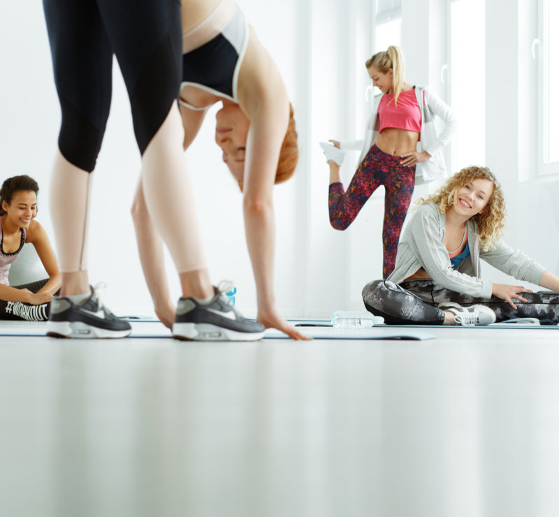 Happy, sportive women stretching after zumba training
